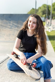 Молодая девушка позирует рядом с скейтборд на открытом воздухе
