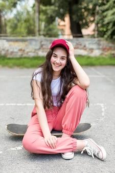 若い女の子が彼女のスケートボードでポーズ