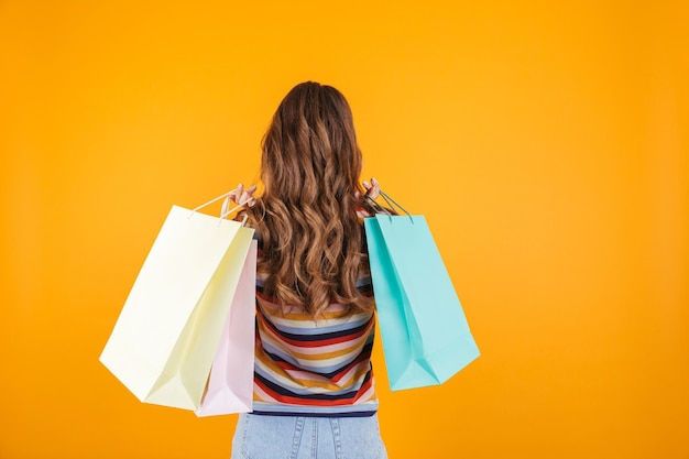 Молодая девушка позирует на желтой стене, держа хозяйственные сумки.