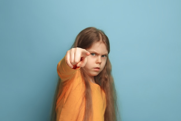 Giovane ragazza in posa e che punta in avanti contro il muro blu