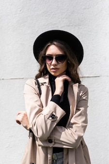 Young girl posing on the street at sunny day, having fun alone, stylish vintage clothes hat and sunglasses. travel concept