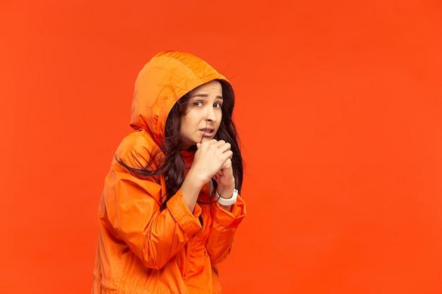 La giovane ragazza in posa in studio in giacca autunnale isolata sul rosso. emozioni negative umane. concetto del freddo. concetti di moda femminile