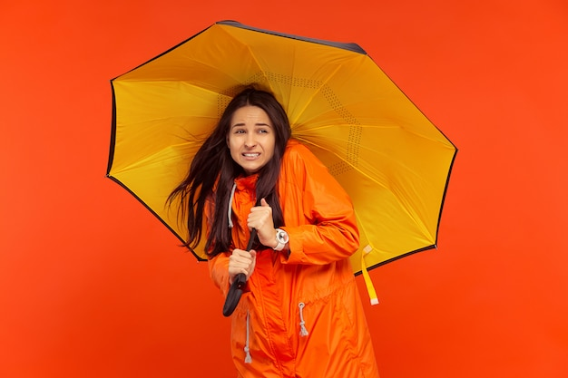 Young girl posing at studio in autumn jacket isolated on red