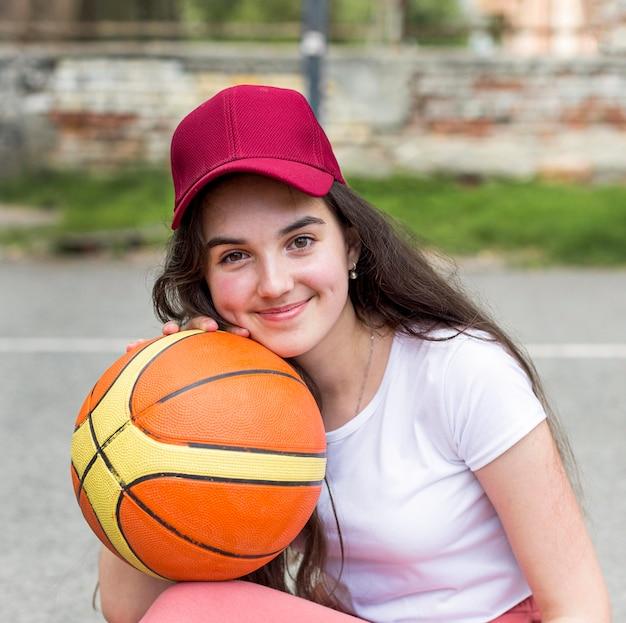 Молодая девушка позирует с баскетболом