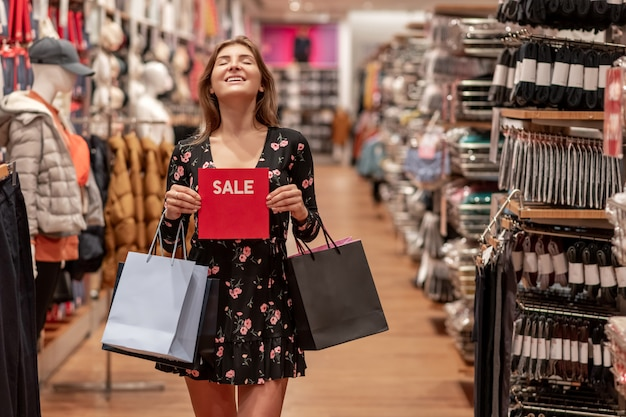 어린 소녀 거래 층의 중간을 따라 걷고 양손에 색된 가방과 함께 빨간색 판매 기호로 포즈. 즐거움의 감정. 매수. 감긴 눈. 판매. 큰 할인.