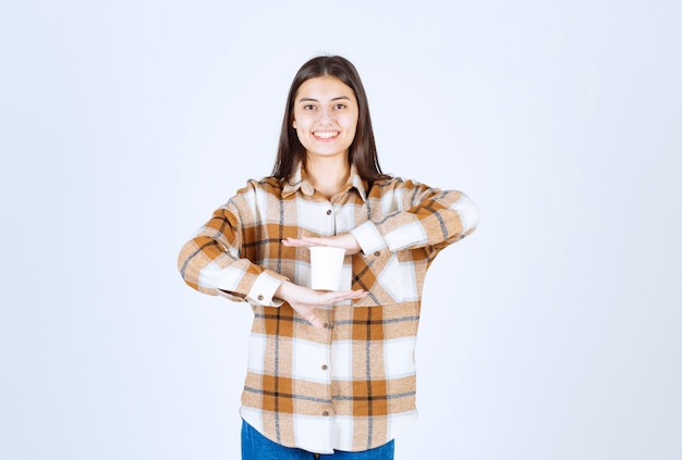 Young girl posing with cup of tea on white wall.