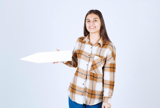 Маленькая девочка позирует с пустым указателем стрелки речи на белой стене.