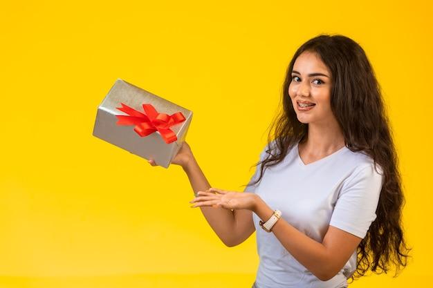 Giovane ragazza in posa con una confezione regalo in mano e sensazione positiva.
