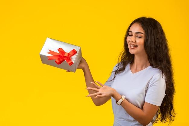 Giovane ragazza in posa con una confezione regalo in mano e guardando ad esso