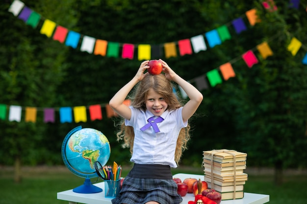 Young girl posing with red newton apple against flags