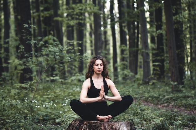 Молодая девушка занимается йогой в лесу, концепция наслаждения уединением и концентрацией, солнечный свет