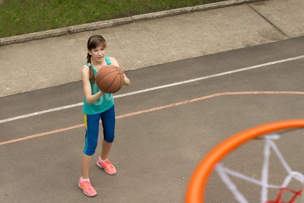フープの上から見た、ゴールを狙ってバスケットボールチームのために練習している少女