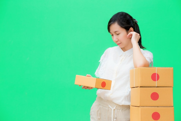 Young girl prepare parcel box for delivery,
