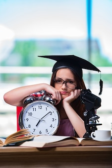 Young girl preparing for exams with large clock