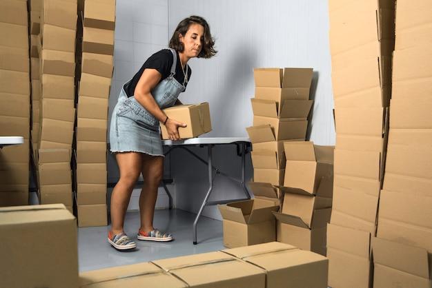 Молодая девушка готовит поставки в картонных коробках на фабрике