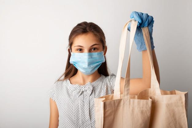 Молодая девушка готовится пойти по магазинам во время эпидемии