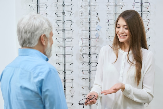 Young girl presenting eyeglasses to old man.