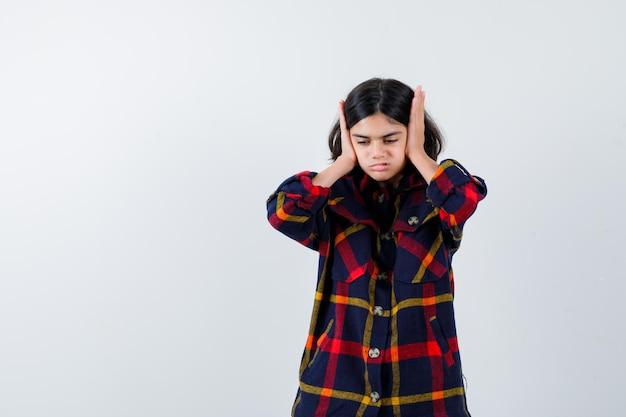 Молодая девушка нажимает уши руками в клетчатой рубашке и выглядит раздраженной, вид спереди.