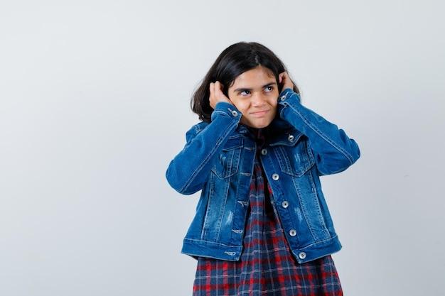 어린 소녀가 귀에 손을 대고 체크 셔츠와 진 재킷을 입고 귀엽게 쳐다보고 있습니다.