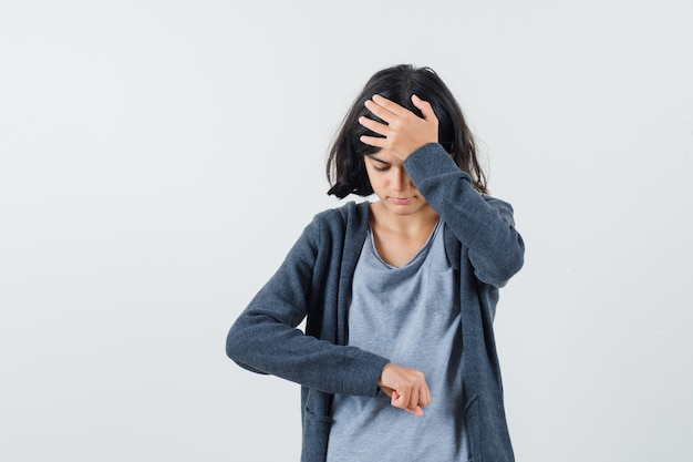 Молодая девушка делает вид, будто смотрит на часы, положив руку на лоб, в светло-серой футболке и темно-серой толстовке с капюшоном на молнии.