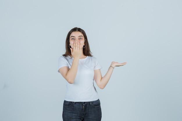 Ragazza che finge di mostrare qualcosa mentre si tiene la mano sulla bocca in t-shirt, jeans e guardando stupito. vista frontale.