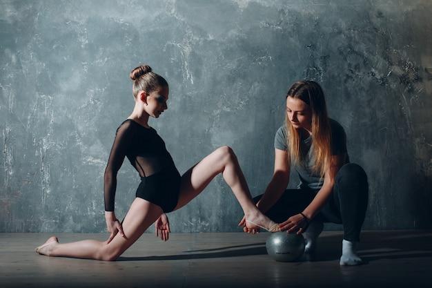 Профессиональная гимнастка маленькой девочки с художественной гимнастикой танца женщины тренера в студии.