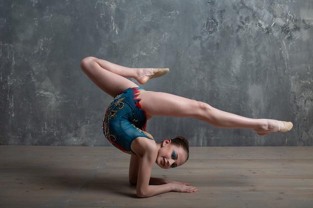 Молодая девушка профессиональная гимнастка женщина танцует художественную гимнастику в студии.