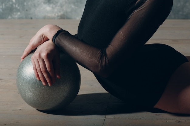 Молодая девушка профессиональная гимнастка танцует художественную гимнастику с мячом в студии.