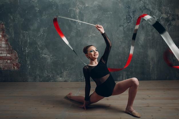 若い女の子のプロの体操選手の女性は、スタジオでリボンで新体操を踊ります。