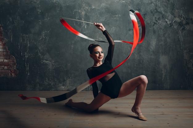 Молодая девушка профессиональная гимнастка танцует художественную гимнастику с лентой в студии.