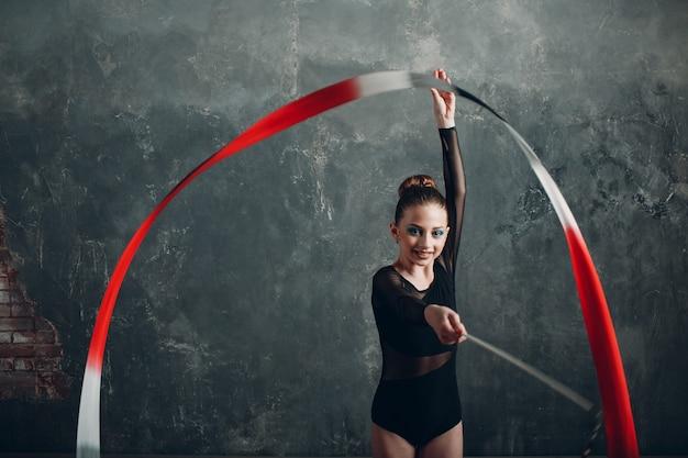 Молодая девушка-профессиональная гимнастка танцует художественную гимнастику с круглой лентой в студии
