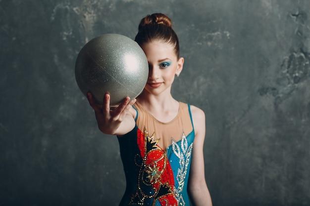 Молодая девушка профессиональный гимнаст женский портрет художественная гимнастика с мячом в студии.