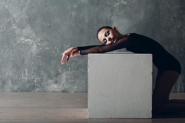 Молодая девушка профессиональная гимнастка женщина художественная гимнастика расслабляющий с белым кубом в студии.