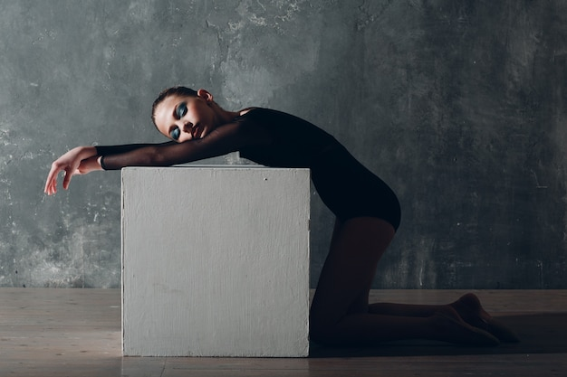 Young girl professional gymnast woman rhythmic gymnastics relaxing with white cube at studio.
