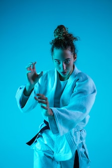 Young girl professional judoist isolated on blue in neon