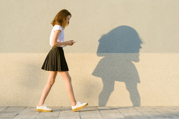 Young girl in the profile, walks along the gray wall with mobile phone
