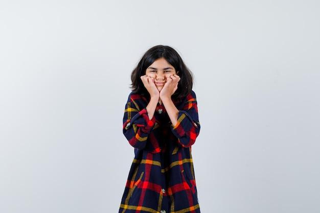 Молодая девушка подпирает подбородок под рукой в клетчатой рубашке и выглядит счастливой, вид спереди.