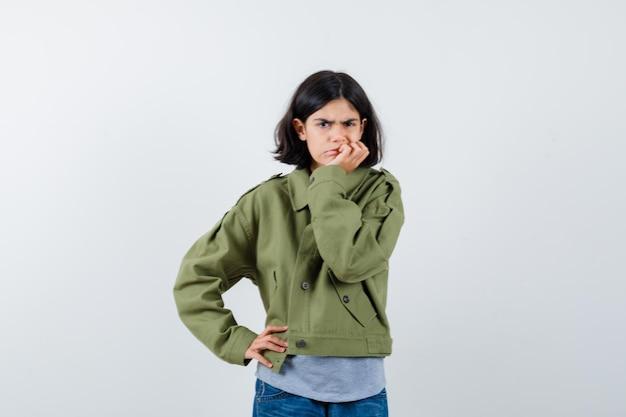 Молодая девушка подпирает подбородок рукой, держа руку на талии в сером свитере, куртке цвета хаки, джинсовых брюках и выглядит задумчиво. передний план.