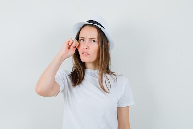 흰색 t- 셔츠, 모자에 그녀의 뺨을 당기고 혼란 스 러 워 보이는 어린 소녀. 전면보기.
