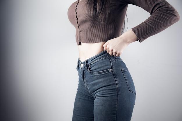 Молодая девушка тянет джинсы на сером фоне
