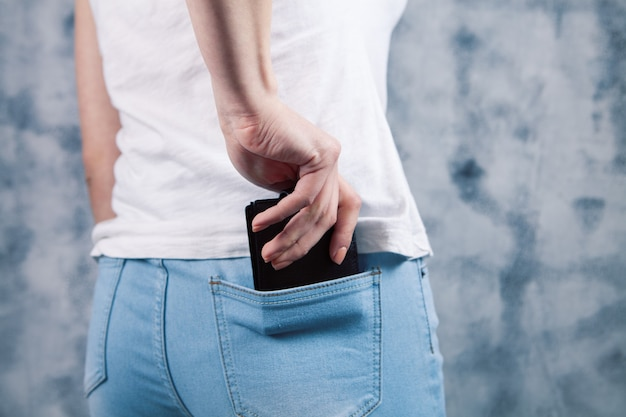 Young girl pulls out a phone from her back pocket on a gray