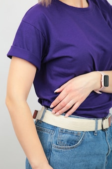 Young girl in purple t-shirt on a grey surface