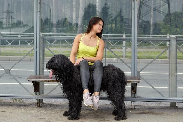 어린 소녀는 대중 교통 역에 앉아 버스를 기다리는 동안 검은 briard에 다리를 댔습니다.
