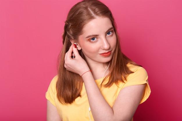 若い女の子はイヤホンを置き、音楽を聴く準備ができて、明るい黄色のtシャツを着て、茶色のストレートの髪をしていて、一人で自由な時間を過ごします。人とentairtaimentのコンセプトです。