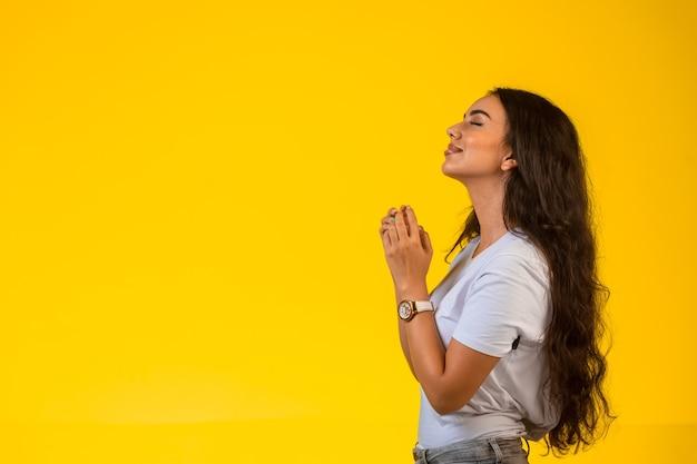 Молодая девушка кладет руки под подбородок и молится на желтом фоне.