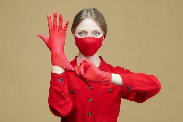 若い女の子は赤い手袋とフェイスマスクを着用します。コロナウイルス感染を予防するための概念19。