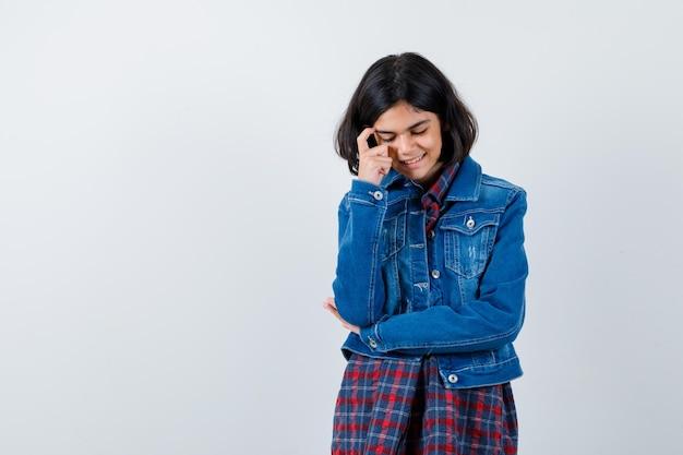 Giovane ragazza che mette il dito sulla tempia, appoggiando la guancia sulla mano in camicia a quadri e giacca di jeans e sembra carina. vista frontale.