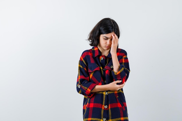 Young girl putting hand on forehead while holding hand on elbow in checked shirt and looking pensive. front view.