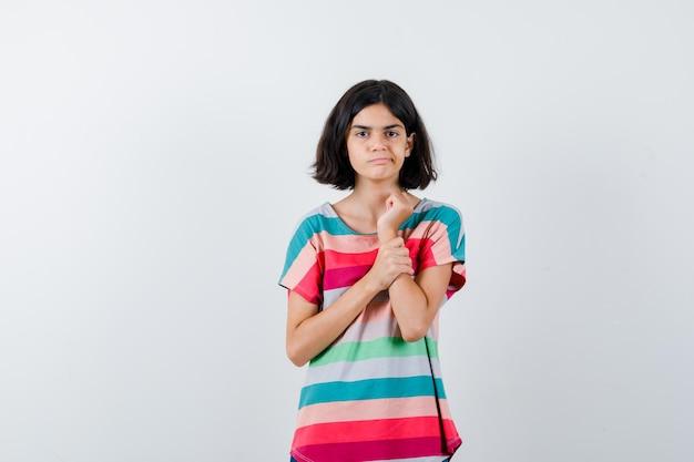 Молодая девушка положила руку на предплечье в красочной полосатой футболке и выглядела серьезной. передний план.