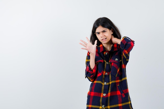 Молодая девушка кладет руку на шею, показывая знак остановки и подмигивая в клетчатой рубашке и выглядя измученной, вид спереди.